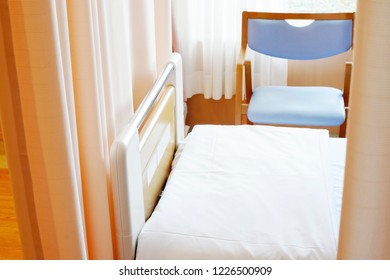 Medical privacy curtain and empty bed in a hospital room