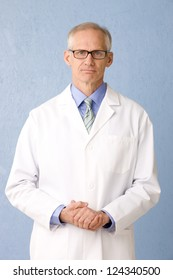 Medical professional in lab coat wearing glasses on blue background three quarter length, looking to camera