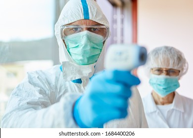 Medical professionals in protective clothing measuring contactless fever at Covid-19 test center during coronavirus epidemic
