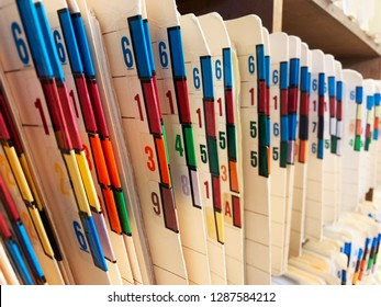 Medical records of patients in numbered and color coded folders are organized and arranged numerically and sequentially in open shelves of a clinic.