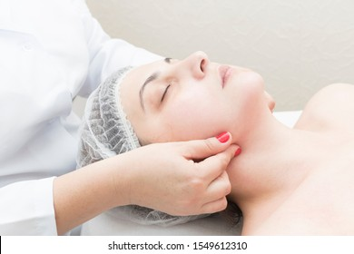 Medical rehabilitation face massage to a young woman in a massage parlor.