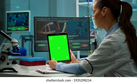 Medical research laboratory portrait of female scientist holding tablet with green chroma key screen. Advanced scientific lab for medicine, biotechnology working for vaccine development.