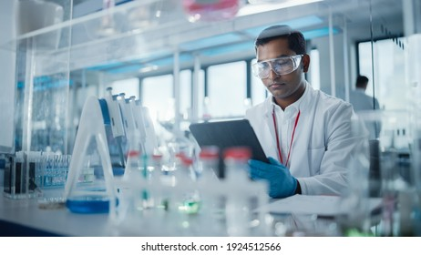 Medical Research Laboratory: Portrait of a Handsome Male Scientist Using Digital Tablet Computer to Analyse Data. Advanced Scientific Lab for Medicine, Biotechnology, Microbiology Development