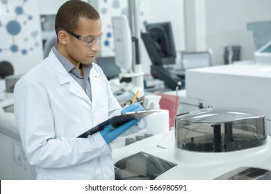 Medical research. Professional chemist young African man writing on his clipboard while working at the laboratory ethnicity profession occupation people medicine clinical biology internship copyspace