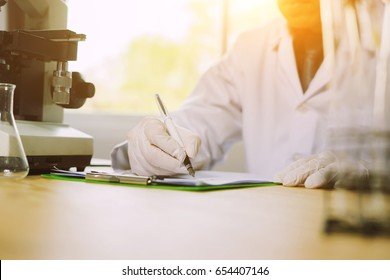 Medical research. Professional chemist young  man writing on his clipboard while working at the laboratory ethnicity profession occupation people medicine clinical biology ,Medical science concept