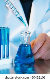 a medical research scientist or chemist works in a laboratory. light in a blue light. blue being a popular color for health, science, calm, relaxation, and just generally a great cool color