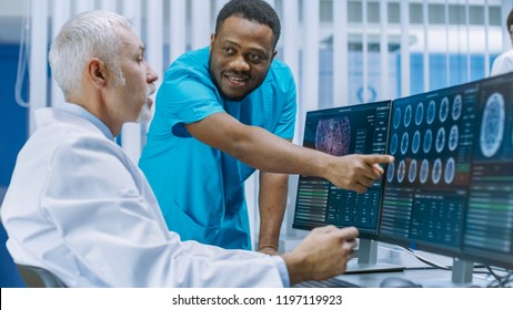 Medical Scientist and Surgeon Discussing CT / MRI Brain Scan Images on a Personal Computer in Laboratory. Neurologists / Neuroscientists in Neurological Research Center Working on a Brain Tumor Cure.