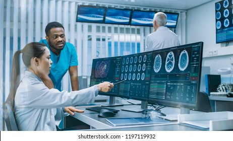 Medical Scientist and Surgeon Discussing CT Brain Scan Images on a Personal Computer in Laboratory. Neurologists / Neuroscientists in Neurological Research Center Working on a Brain Tumor Cure.