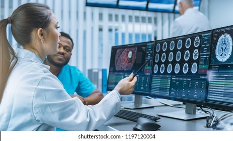 Medical Scientist and Surgeon Discussing CT Brain Scan Images on a Personal Computer in Laboratory. Neurologists /Neuroscientists in Futuristic Neurological Research Center Working on Brain Tumor Cure