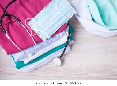 medical scrub shirt with stethoscope on wooden desktop.