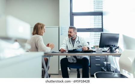 Medical specialist discussing with female patient in his clinic. Doctor with patient during consultation in medical office.