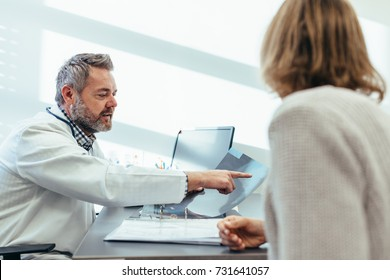 Medical specialist discussing medical scan results with female patient in his clinic. Doctor showing x-ray to patient in medical office.