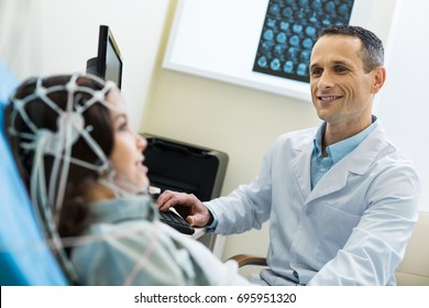 Medical specialist recording electroencephalographic waves of patients brain