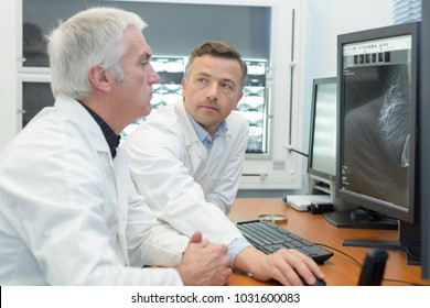 medical specialist studying an mri result from the computer