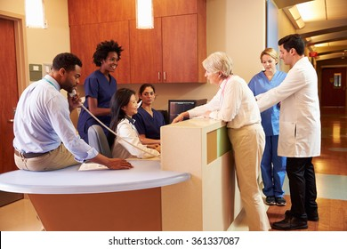 Medical Staff At Busy Nurse's Station In Hospital