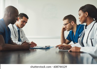 Medical staff meeting. Group of young people in white coats and blue uniform sitting at table in front of each other. Low angle side view with copy space