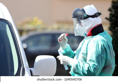 Medical staff member with mask and protective equipment performs Coronavirus nasal swabs test tubes at drive-through testing point in an effort to curb the spread of COVID-19 (novel coronavirus)