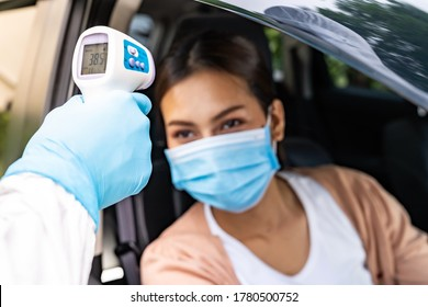 Medical staff with PPE Take Temperature for fever to asian woman before coronavirus covid-19 test at drive thru station in hospital. New normal healthcare drive thru service and medical concept.