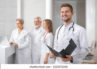 Medical staff of professional, private hospital. Handsome male doctor standing, looking at camera and smiling. Man holding folder and having stethoscope on neck. Group of physicians posing behind.