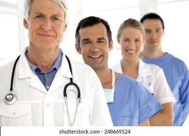 Medical staff standing in a row behind senior doctor leader