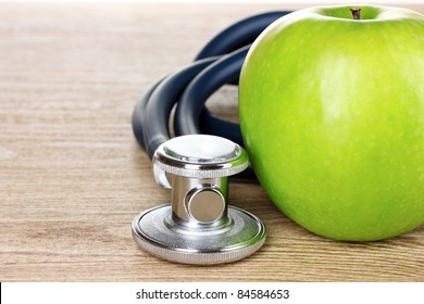Medical stethoscope and apple on wooden background