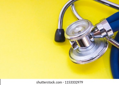 Medical stethoscope with blue tubes are on yellow uniform background view from above with clear area of half photo for labels, headers. Concept photo for diagnosis, scientific research in medicine