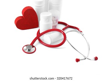 Medical stethoscope with bottles of pills and red heart isolated on white