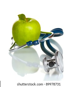 Medical stethoscope and green apple isolated on white