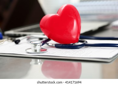 Medical stethoscope head and red toy heart lying on cardiogram chart closeup. Cardio therapeutist, physician make cardiac physical, heart rate measure, arrhythmia, resuscitation and pacemaker concept