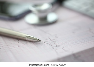 Medical stethoscope head and silver pen lying on cardiogram chart closeup. Cardio therapeutist pulse graph cardiac physical heart rate measure arrhythmia 911 er and resuscitation concept