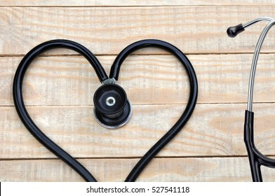 Medical stethoscope in a heart shape on wood table background