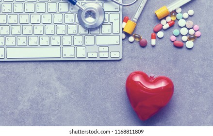 Medical stethoscope and laptop computer , pills on desk