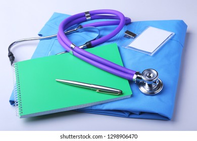 Medical stethoscope lying on a blue doctor's form and notepad close-up. the therapist's work space.