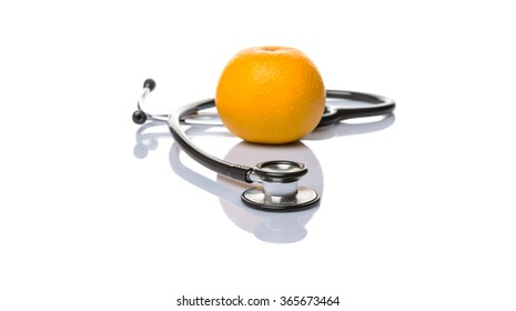 Medical stethoscope with an orange fruit over white background. Healthy lifestyle concept image.