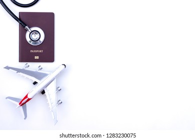 Medical stethoscope, passport and airplane model isolated on white background with copy space. Business trip and travel insurance concept.