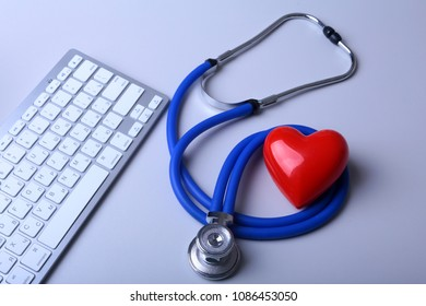 A medical stethoscope with red heart near a laptop on a wooden table