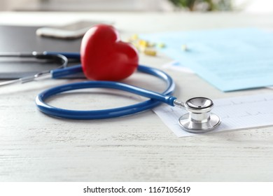 Medical stethoscope and red heart on white wooden table. Cardiology concept