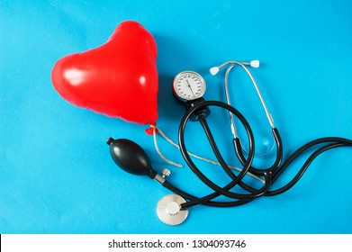 Medical stethoscope with red вalloon heart on blue. Medical concept. American Heart Month