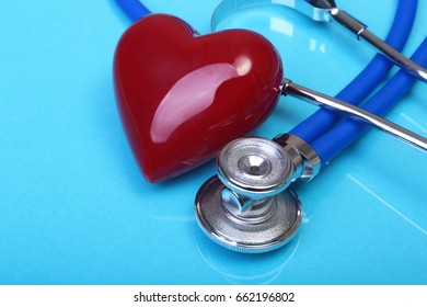 medical stethoscope and red heart on blue mirror background. selective focus.