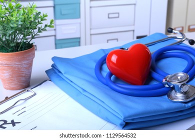 A medical stethoscope with red heart and RX prescription are lying on a medical uniform
