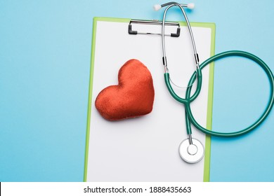 medical stethoscope and red textile heart on blue background, top view