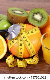 Medical stethoscope and tape measure with fresh ripe fruits and glass of juice on wooden board, healthy lifestyles and nutrition