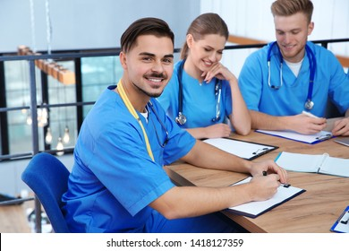 Medical student with groupmates in university library