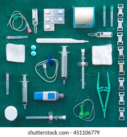 Medical supplies in a square flat lay on a table. Including syringes, bandages, pills and other hospital equipment.