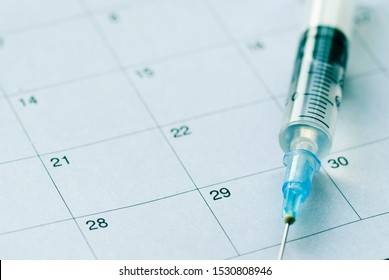 Medical syringe with transparent vaccine on white calendar background. Vaccination schedule concept with copy space