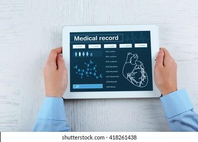 Medical tablet in doctor hands on light background