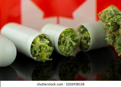 Medical tablets of Cannabis - marijuana   white capsules on the black mirror  background with Canada flag.
