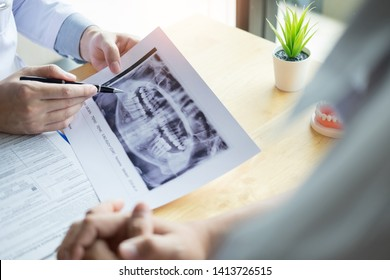 Medical team discussing, health care talking to female patient, Medical conferrence concept, doctor holding and looking at dental x-ray attending a client