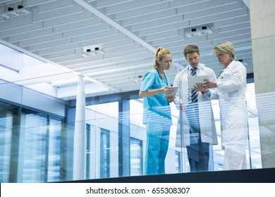 Medical team discussing over digital tablet in corridor at hospital
