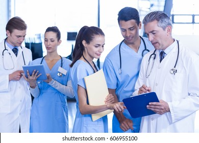Medical team discussing paperwork on clipboard at the hospital